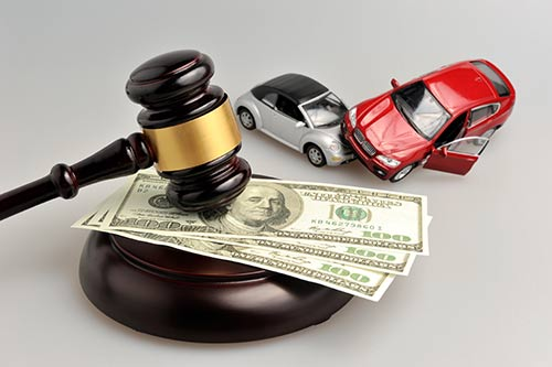 This image shows several hundred dollar bills under a judge's gavel, and two toy cars crashing into each other.