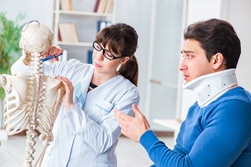 This image shows a doctor using a model skeleton to explain whiplash to a young man who has a neck brace.