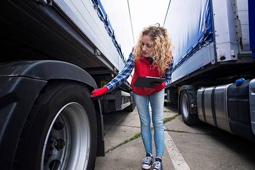 This image shows a truck driver checking her vehicle's tires.
