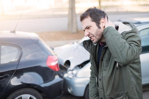 A man holding his neck after an Uber accident.