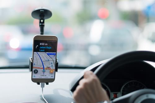 A driver using the Uber app to drive a passenger to their destination.